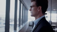 Mature businessman looking outside the window video