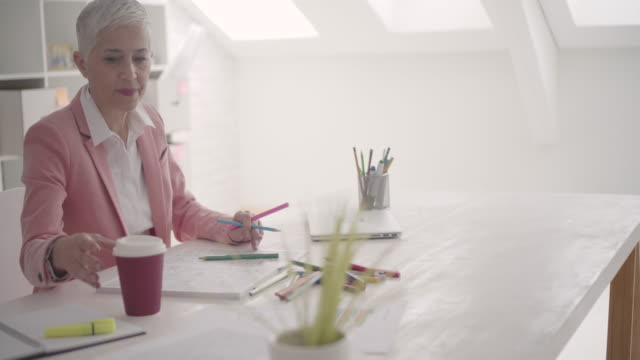 4K: Mature Businesswoman Coloring Book In Her Office. video