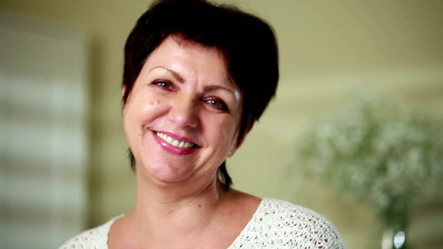 Mature charming woman smiling at the camera in the interior. Close up. Dolly shot. video