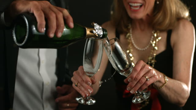 Mature couple at New Year's Party pouring champagne video