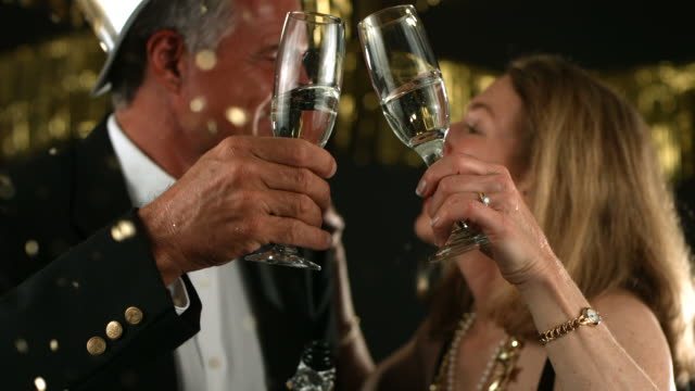 Mature couple at New Year's Party toasting, slow motion video