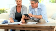 Mature couple calculating their domestic bills video