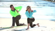 Mature couple doing yoga exercises on the beach video