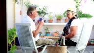 Mature Couple enjoying coffee in courtyard garden video