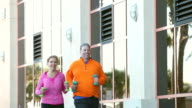 Mature couple exercising, jogging with hand weights video
