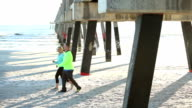 Mature couple exercising, walking on beach video