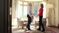 Mature couple greeting each other in living room video