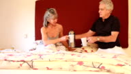 Mature couple having breakfast in bed at home video