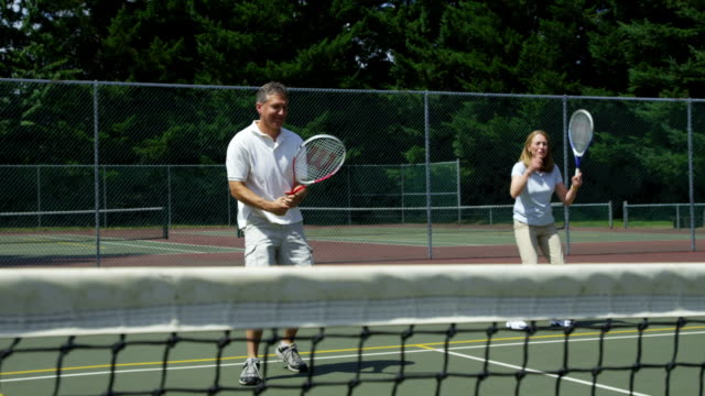 Mature couple playing tennis video