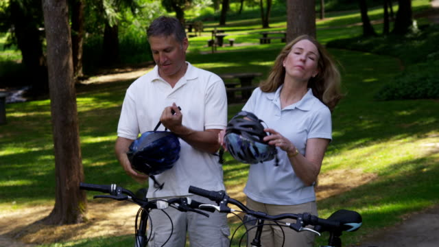 Mature couple putting on bicycle helmets video