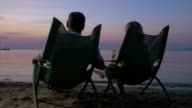 Mature couple relaxing on the beach and drinking cocktails video