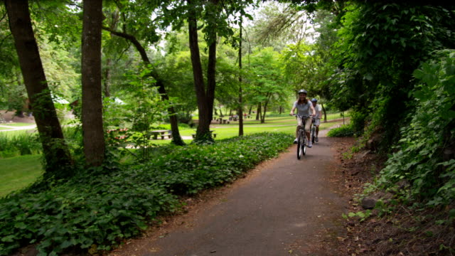 Mature couple riding bicycles at park, slow motion video