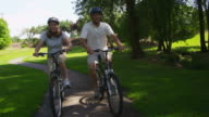 Mature couple riding bicycles, slow motion video