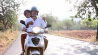Mature Couple Riding Motor Scooter Along Country Road video
