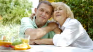 Mature couple sitting in an embrace in the garden. video
