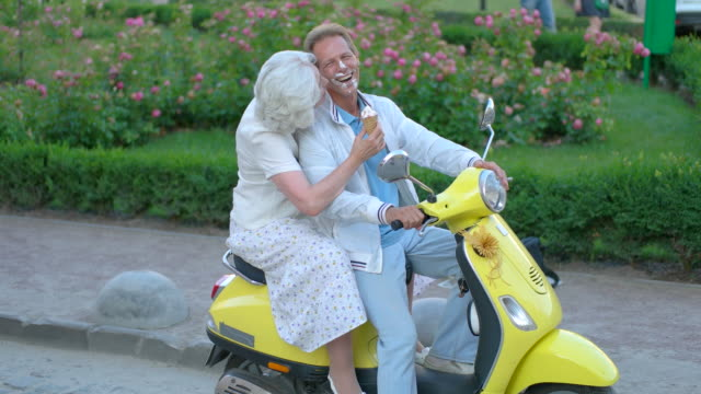 Mature couple sitting on scooter. video