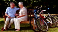 Mature couple talking together in a park video