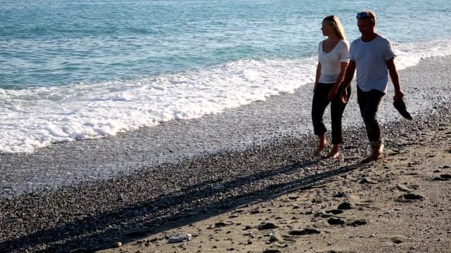 Mature couple walk along surf edge, talking video