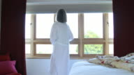 Mature female getting up and walking to window video