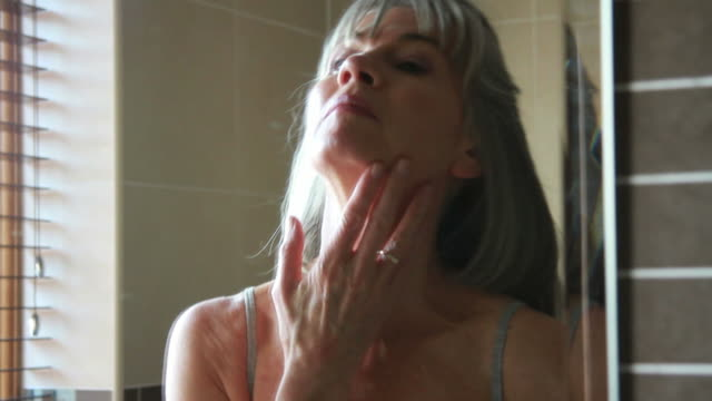 Mature female in bathroom applying crème video