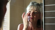 Mature female in bathroom, applying eye cream video