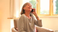 Mature female talking on phone at home video