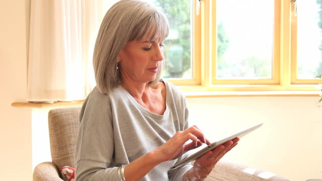 Mature female with computer tablet at home video