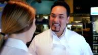 Mature Hispanic chef in Tex-Mex restaurant, training waitress in kitchen video