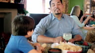 Mature Hispanic father having meal in restaurant with young son video