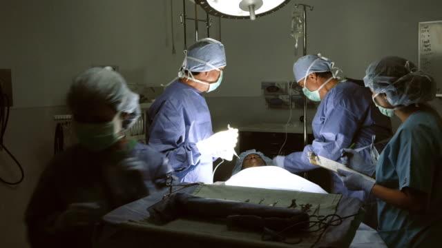 Mature Hispanic surgeon instructs young Asian nurse video
