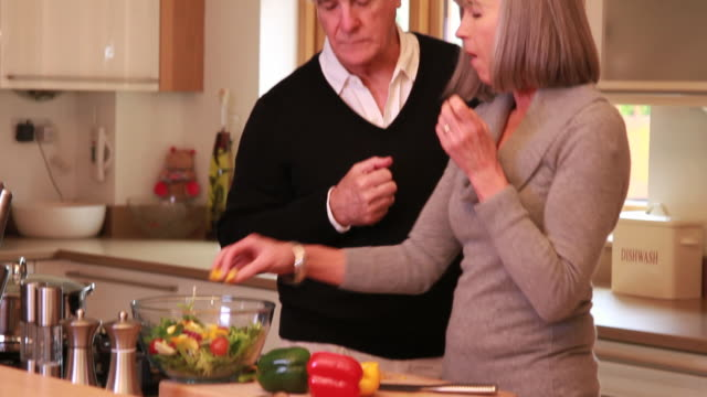 Mature male and female cooking together in kitchen video