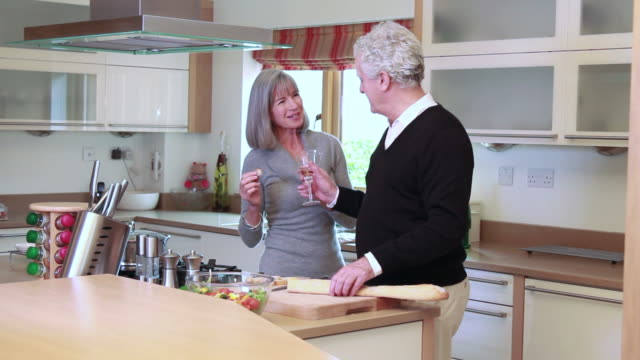 Mature male and female drinking in kitchen video