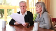 Mature male and female looking at paperwork video