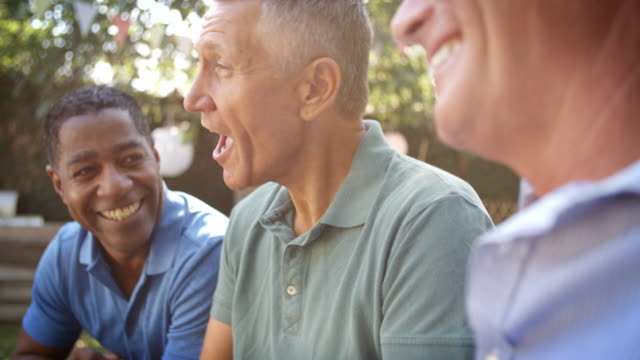 Mature Male Friends Socializing In Backyard Together video