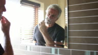 Mature male shaving and looking in mirror video
