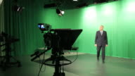Mature male TV presenter walking out of studio video