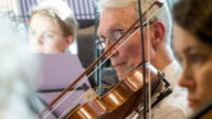 Mature male violinist in orchestra video