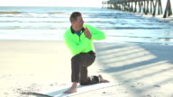 Mature man doing yoga exercises on the beach video