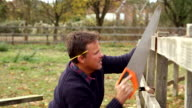 Mature Man Fixing Outdoor Fence With Saw video