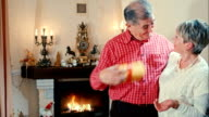 Mature man giving a present to wife near fireplace video