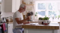 Mature Man In Kitchen Has Breakfast Whilst Reading Newspaper video