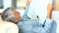 Mature man reading newspaper while lying on sofa video