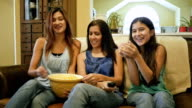 Mature mother and teen daughters watching television and eating popcorn together video