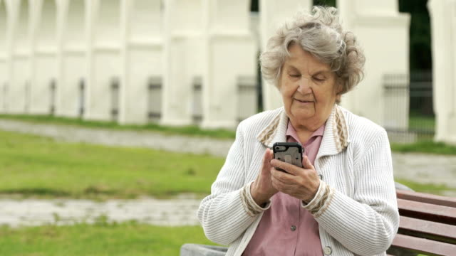 Mature old woman holds silver smart phone outdoors video
