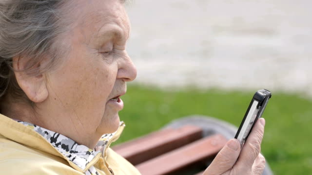 Mature old woman talking on mobile phone outdoors video