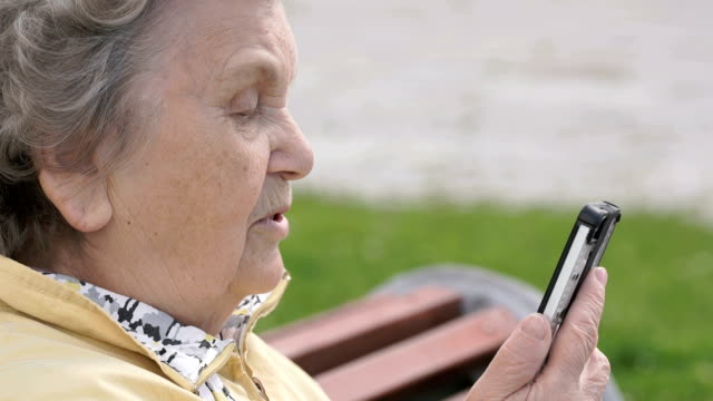 Mature old woman talking on smartphone outdoors video