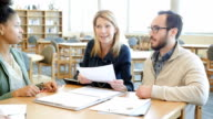 Mature professor explaining something to diverse study group video