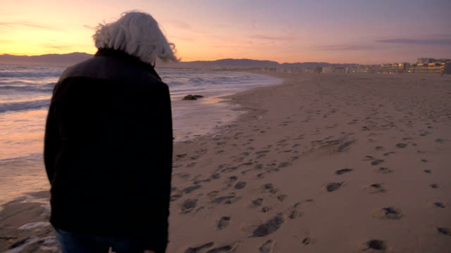 Mature senior woman walking on sand beach excited and happy at sunset video