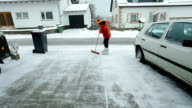 Mature woman cleaning snow in front of her house video