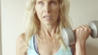 A mature woman does curls in her home gym. video